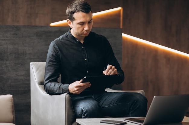 Hübscher geschäftsmann, der am computer im büro arbeitet