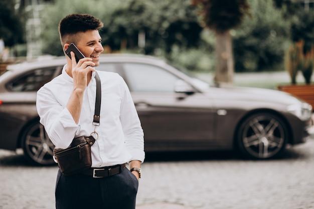 Hübscher geschäftsmann, der am telefon durch sein auto spricht