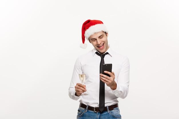 Hübscher geschäftsmann, der am telefon spricht und glas champagner hält, der chirstmas feiert