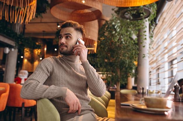 Hübscher geschäftsmann, der an computer arbeitet und kaffee in einem café trinkt