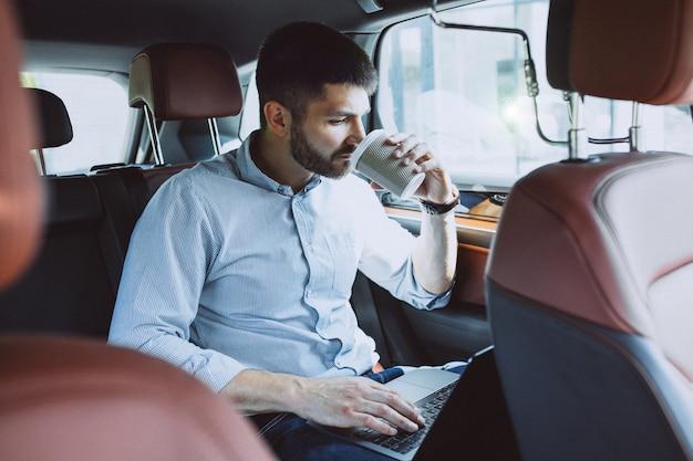 Hübscher geschäftsmann, der an einem computer im auto arbeitet