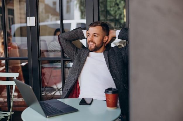 Hübscher geschäftsmann, der an laptop im café arbeitet