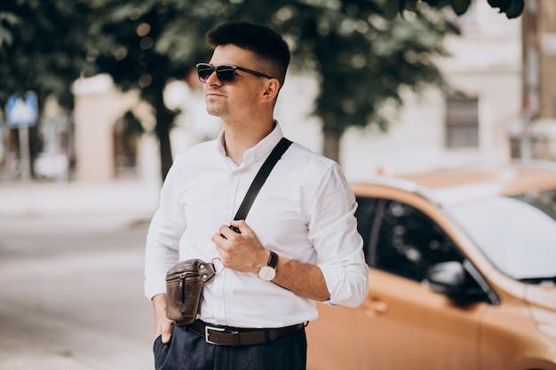 Hübscher geschäftsmann, der an seinem auto auf einer geschäftsreise steht
