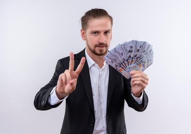 Hübscher geschäftsmann, der anzug hält, der bargeld zeigt und nummer zwei zeigt, die zuversichtlich steht, über weißem hintergrund zu stehen
