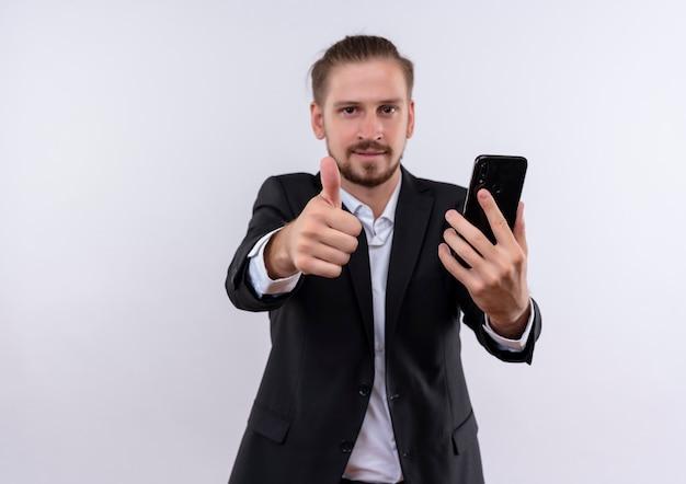 Hübscher geschäftsmann, der anzug hält, der lächelndes smartphone hält, zeigt daumen hoch, die über weißem hintergrund stehen