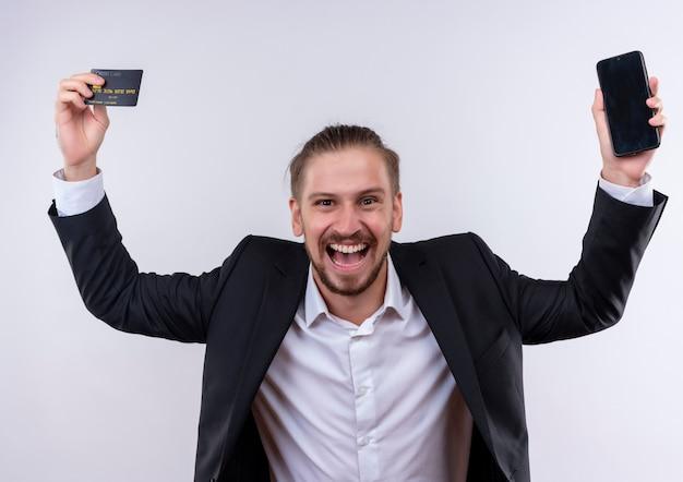 Hübscher geschäftsmann, der anzug hält, der smartphone und kreditkarte in den erhöhten hatten glücklich und aufgeregt über weißem hintergrund steht