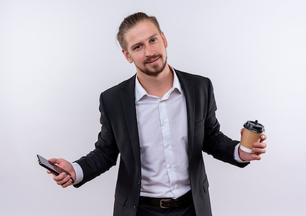 Hübscher geschäftsmann, der anzug hält kaffeetasse und smartphone betrachtet kamera mit lächeln auf gesicht, das über weißem hintergrund steht