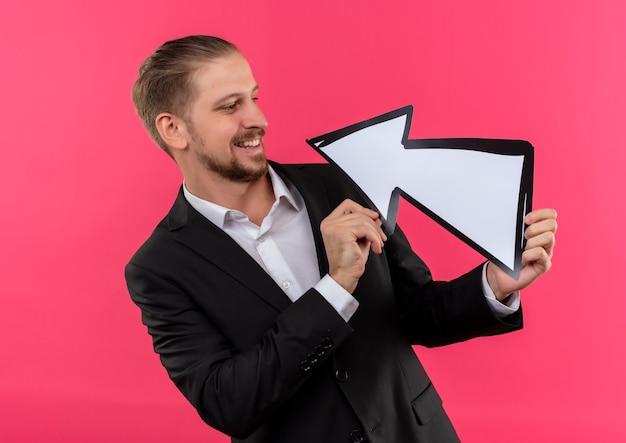 Hübscher geschäftsmann, der anzug hält pfeilzeichen loking am lächelnden stehen über rosa hintergrund