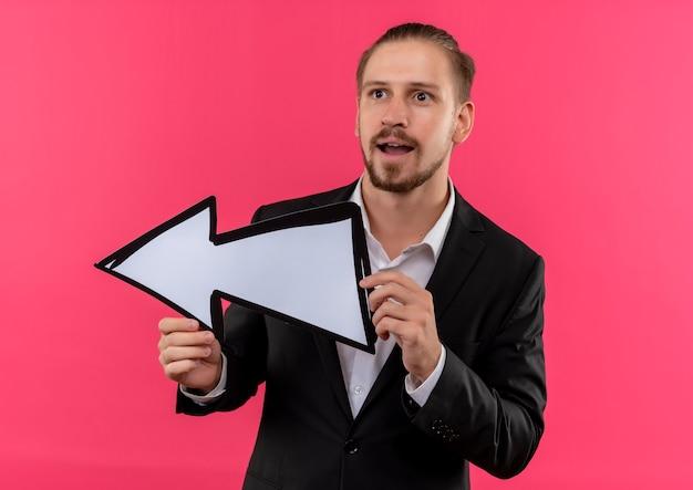 Hübscher geschäftsmann, der anzug hält pfeilzeichen schaut asie überrascht steht über rosa hintergrund
