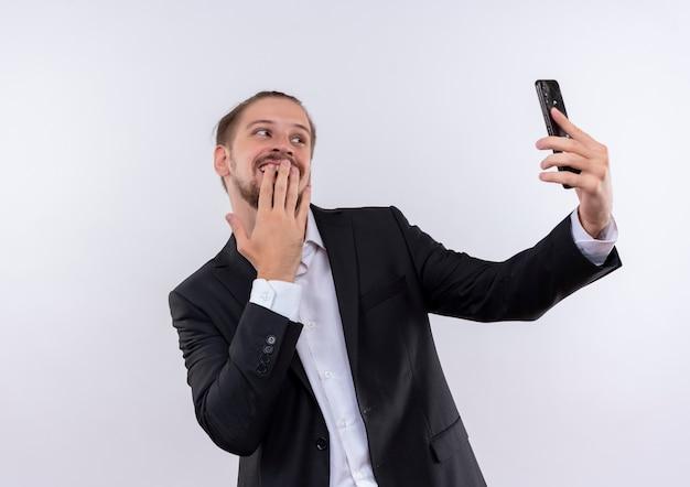 Hübscher geschäftsmann, der anzug hält smartphone hält selfie mit schüchternem lächeln auf gesicht steht über weißem hintergrund