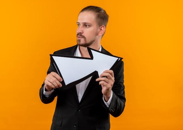 Hübscher geschäftsmann, der anzug hält weißen pfeil, der beiseite mit lächeln auf gesicht steht, das über orange hintergrund steht
