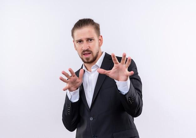Hübscher geschäftsmann, der anzug trägt, der arme mit angewidertem ausdruck heraushält, der über weißem hintergrund steht