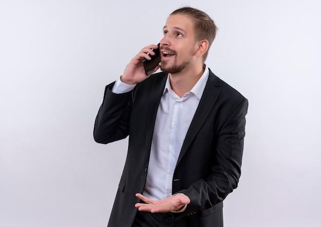 Hübscher geschäftsmann, der anzug trägt, der auf handy glücklich und positiv steht über weißem hintergrund spricht