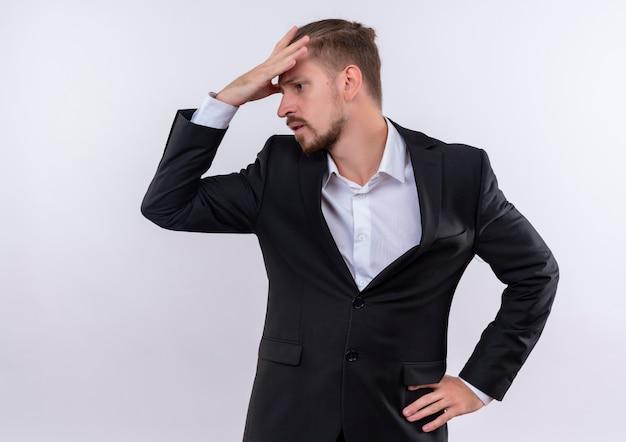 Hübscher geschäftsmann, der anzug trägt, der beiseite schaut, verwechselt mit hand über kopf, der über weißem hintergrund steht