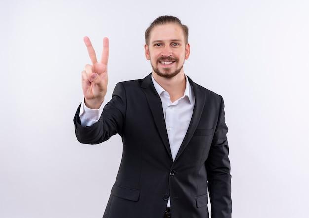 Hübscher geschäftsmann, der anzug trägt, der kamera lächelnd zeigt, siegt zeichen, das über weißem hintergrund steht