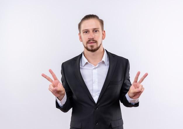 Hübscher geschäftsmann, der anzug trägt, der kamera lächelnd zeigt siegzeichen mit beiden händen steht über weißem hintergrund