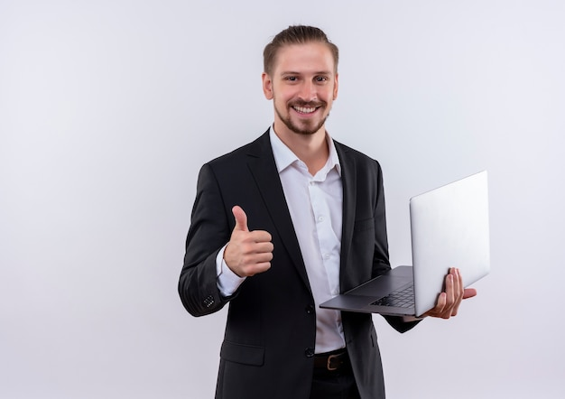 Hübscher geschäftsmann, der anzug trägt, der leere seiten hält, die kamera betrachten, die fröhlich daumen zeigt, die oben über weißem hintergrund stehen