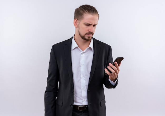 Hübscher geschäftsmann, der anzug trägt, der sein smartphone verwirrt über weißem hintergrund stehend betrachtet