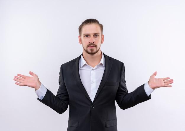 Hübscher geschäftsmann, der anzug trägt, der verwirrte achselzucken steht, die über weißem hintergrund stehen