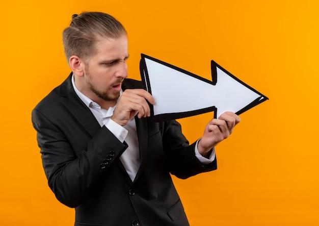 Hübscher geschäftsmann, der anzug trägt, der weißen pfeil hält, der damit zur seite schaut, verwirrt verwirrt über orange hintergrund stehend