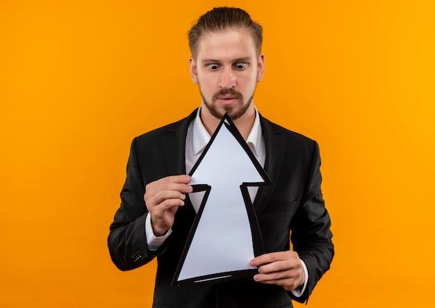 Hübscher geschäftsmann, der anzug trägt, der weißen pfeil hält, der ihn verwirrt und überrascht betrachtet, der über orange hintergrund steht