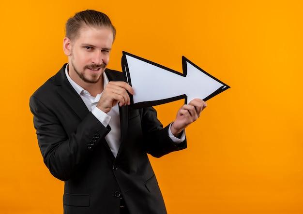 Hübscher geschäftsmann, der anzug trägt, der weißen pfeil hält, der kamera betrachtet, die über orange hintergrund steht und zwinkert
