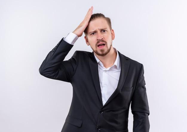 Hübscher geschäftsmann, der anzug trägt kamera betrachtet verwirrt mit hand auf kopf für fehler, der über weißem hintergrund steht