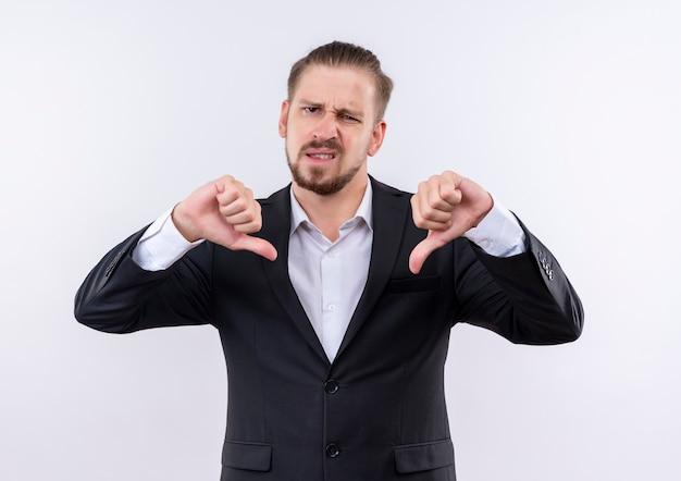 Hübscher geschäftsmann, der anzug trägt kamera unzufrieden zeigt daumen unten stehend über weißem hintergrund