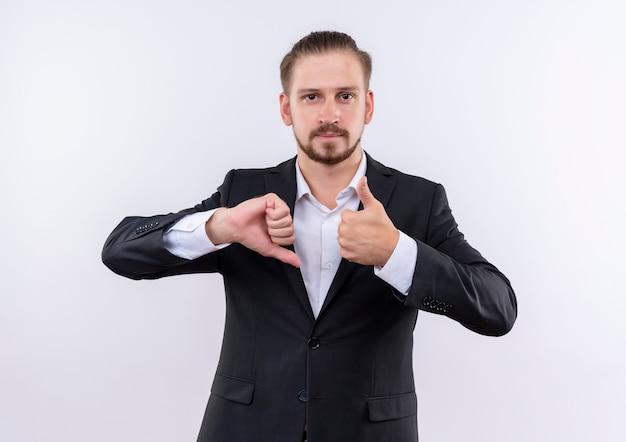 Hübscher geschäftsmann, der anzug trägt, zeigt daumen oben und unten stehend über weißem hintergrund