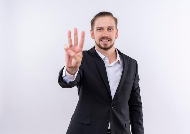 Hübscher geschäftsmann, der anzug zeigt und mit den fingern nummer drei über weißem hintergrund stehend zeigt