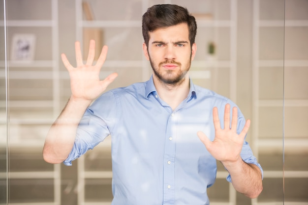 Hübscher geschäftsmann, der auf glasschirm im büro drückt.