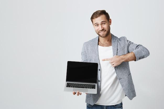 Hübscher geschäftsmann, der auf laptop-bildschirm zeigt