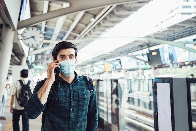 Hübscher geschäftsmann, der chirurgische gesichtsmaske gegen neuartiges coronavirus oder coronavirus-krankheit trägt und smartphone am öffentlichen himmelsbahnhof verwendet