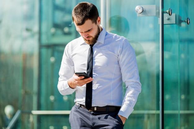 Hübscher geschäftsmann, der durch mobiltelefon simst