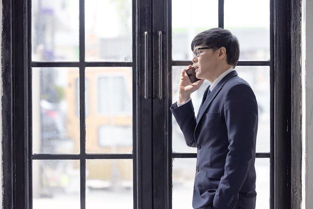 Hübscher geschäftsmann, der e-mails am telefon in der nähe des fensters überprüft