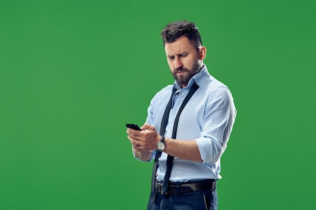 Hübscher geschäftsmann, der e-mails am telefon überprüft. ernster geschäftsmann, der lokal auf grün steht. schönes männliches halblanges porträt