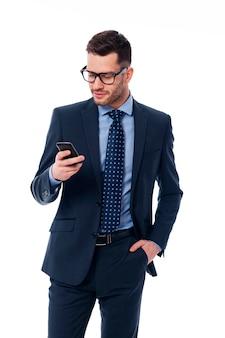 Hübscher geschäftsmann, der e-mails am telefon überprüft