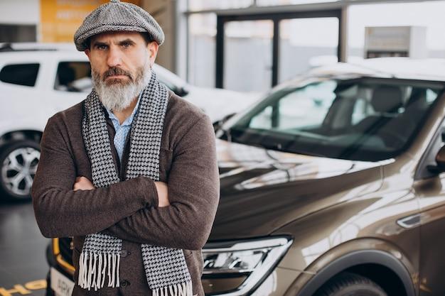 Hübscher geschäftsmann, der ein auto im autohaus wählt