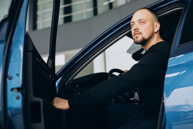 Hübscher geschäftsmann, der ein auto in einem autoausstellungsraum wählt