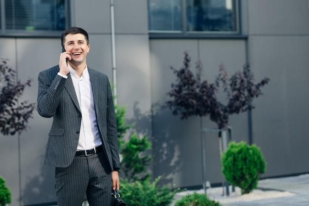 Hübscher geschäftsmann, der einen klassischen anzug trägt, der auf straße nahe bürozentrum geht und auf handy spricht. geschäftsleute.