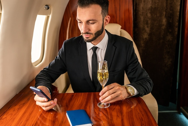 Hübscher geschäftsmann, der eleganten anzug trägt, der auf exklusivem privatjet fliegt