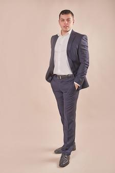 Hübscher geschäftsmann, der grauen anzug trägt