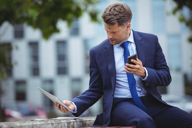 Hübscher geschäftsmann, der handy hält, während digitales tablett verwendet