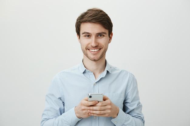 Hübscher geschäftsmann, der handy, lächelnd verwendet