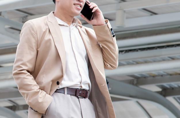 Hübscher geschäftsmann, der handy oder intelligentes telefon in der modernen stadt verwendet.