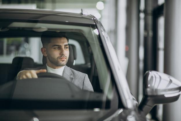 Hübscher geschäftsmann, der im auto fährt