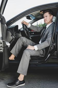 Hübscher geschäftsmann, der im auto mit offener tür sitzt