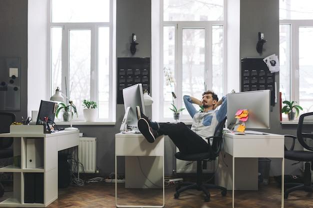 Hübscher geschäftsmann, der im büro arbeitet