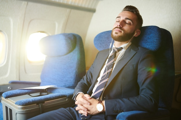 Hübscher geschäftsmann, der im flugzeug schläft