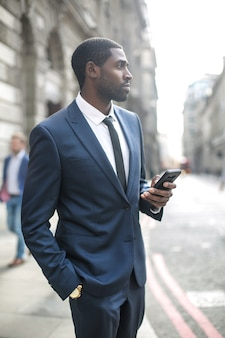 Hübscher geschäftsmann, der in die straße, sein telefon überprüfend geht